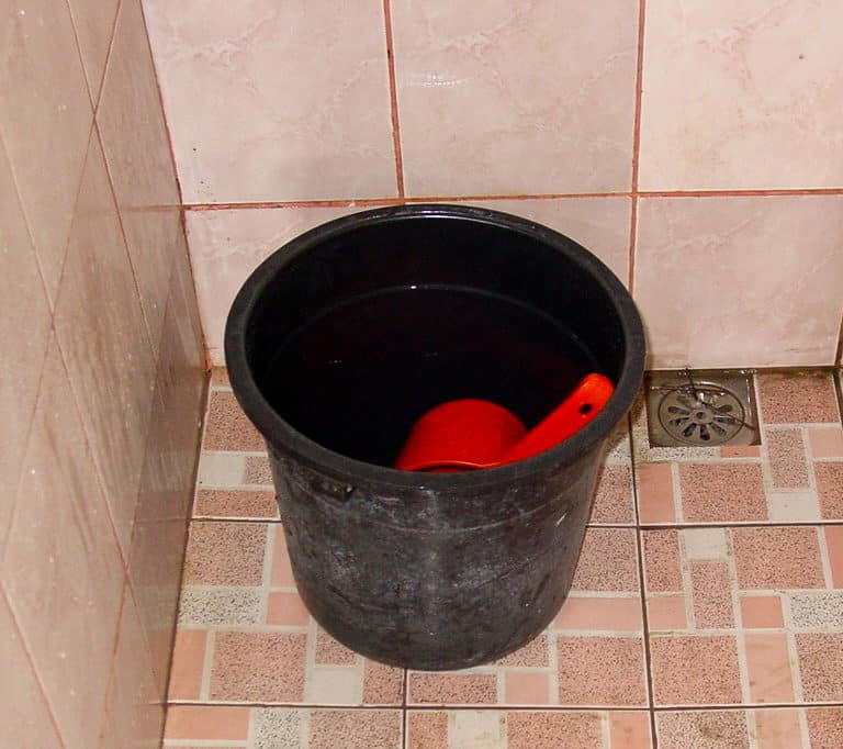 The Philippines Tabo. A black bucket on the floor with a red pail