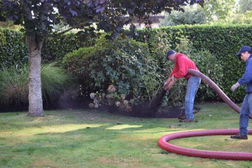 man blowing compost on a lawn
