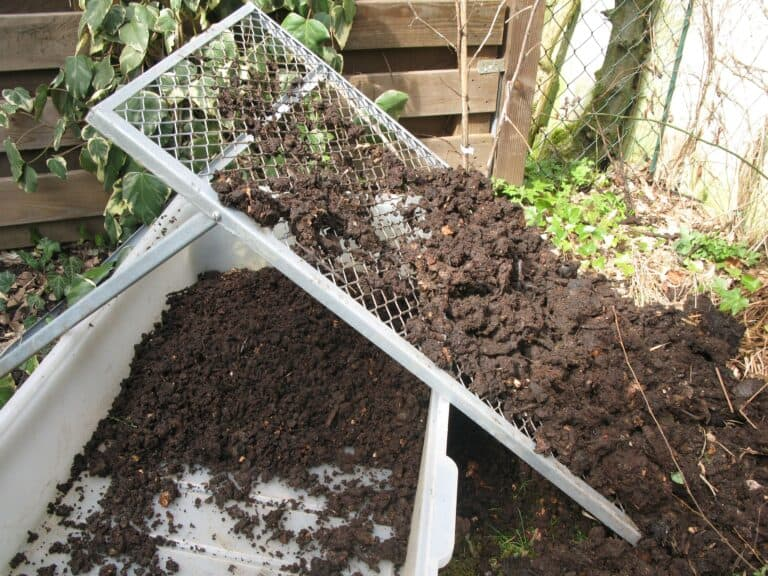 clumpy compost being put through a screener