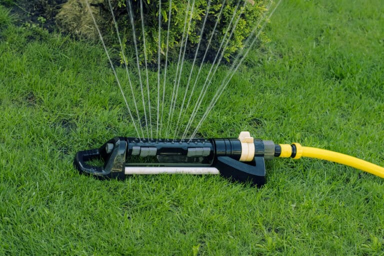 Automatic sprinkler on a green lawn background