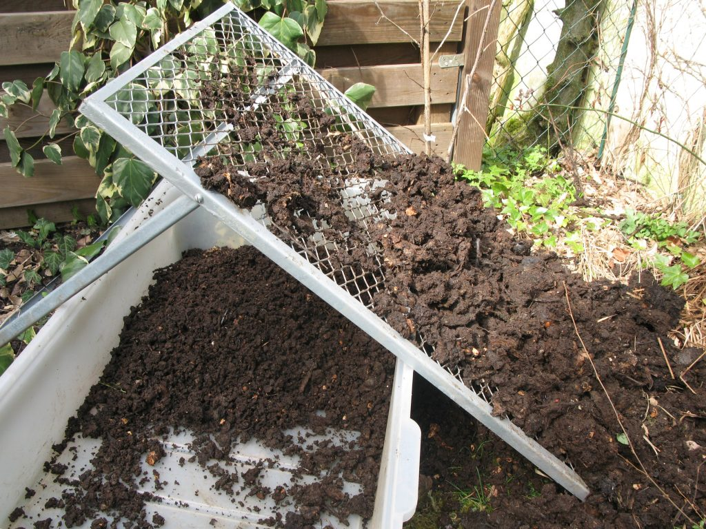Sieving compost with a coarse sieve